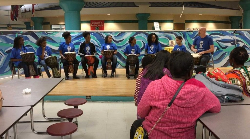 Students playing drums with parents watching